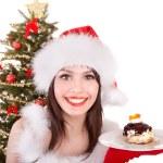 Girl in santa hat eat cake by christmas tree. — Stock Photo