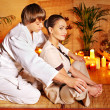 Male masseur doing massage woman in bamboo spa. — Stock Photo