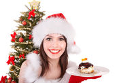 Girl in santa hat eat cake by christmas tree. — Stock Photo