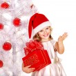 Child in Santa hat with gift box near white Christmas tree. — Stock Photo #14621231