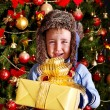 Child with gift box near Christmas tree. - Стоковая фотография