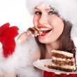 Foto Stock: Girl in Santa hat eat cake .