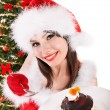 图库照片: Christmas girl in red santa hat and cake on plate.