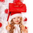 Child in Santa hat with gift box near white Christmas tree. — Stock Photo