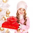 Child in hat and mittens holding Christmas red gift box . — Stock Photo #14621355