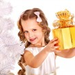 Child with gift box near white Christmas tree. - Foto Stock