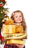 Child with gift box near Christmas tree. — Stockfoto