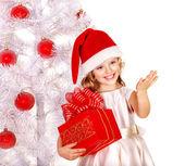 Dítě v santa hat s krabičky poblíž bílé vánoční stromeček. — Stock fotografie