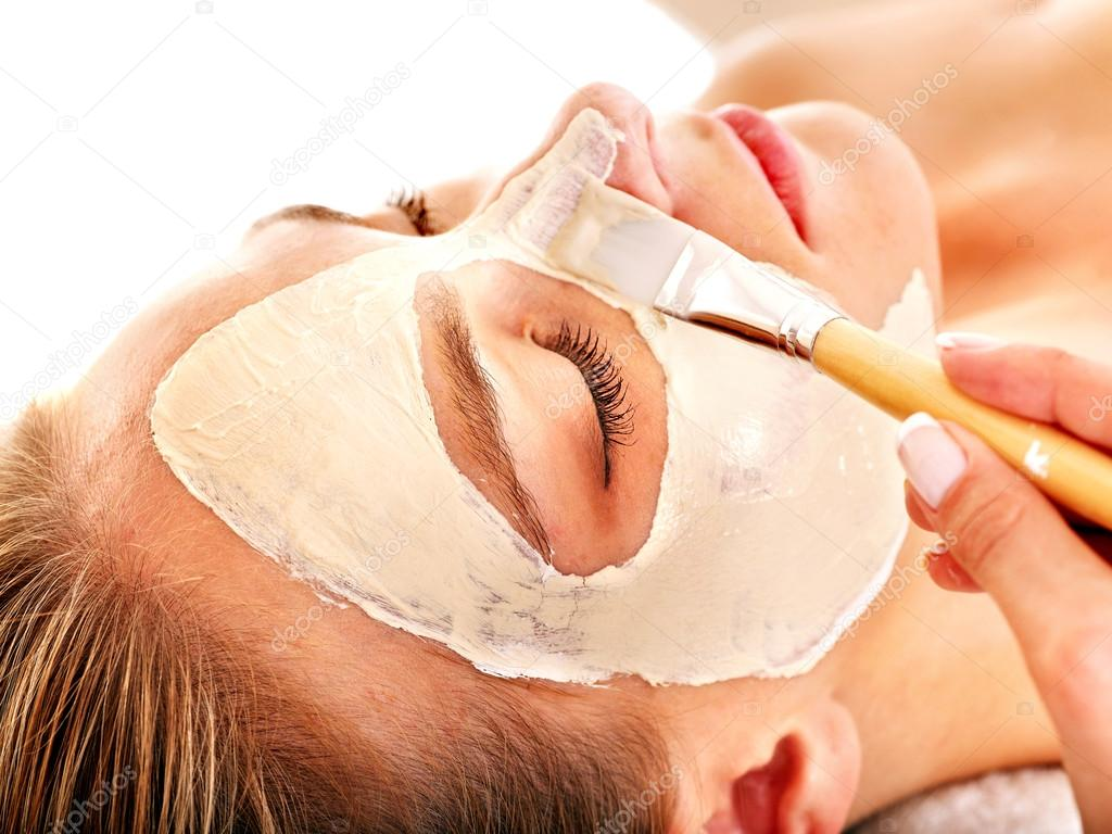 Woman with clay facial mask in beauty spa. Isolated. — Stock Photo #14621367