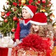 Children in Santa hat with gift box near Christmas tree. — Stock Photo
