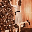 Woman dressing Christmas tree. — Stock Photo