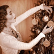 Woman dressing Christmas tree. - Stock Photo
