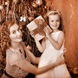 Kid with mother receiving gifts under Christmas tree. - Stock Photo