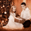 Children  receiving gifts under Christmas tree. - Stock Photo
