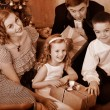 Family with children  receiving gifts under Christmas tree. — Stockfoto