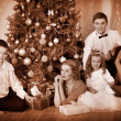 Family with children receiving gifts under Christmas tree. — Stock Photo