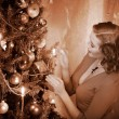 Woman ignites candles on Christmas tree. — Stock Photo #14917823