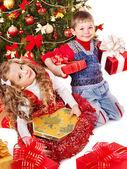 Children with gift box near Christmas tree. — Stock Photo