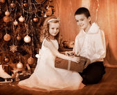 Children receiving gifts under Christmas tree. — Stock Photo