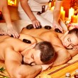 Woman and man getting stone therapy massage in spa. - Stock Photo