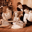 Family with children  receiving gifts under Christmas tree. - Stock Photo