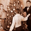 Family with children round dance  Christmas tree. - Stock Photo