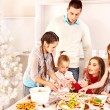 Family with children rolling dough in Xmas kitchen. - Stock Photo