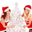 Girl in Santa hat holding Christmas tree. — Stock Photo
