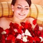 Beautiful young woman in rose petal swim water. — Stock Photo
