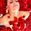 Beautiful young woman in rose petal swim water. — Stock Photo