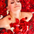 Beautiful young woman in rose petal swim water. - Stock Photo