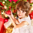 Child with gift box near Christmas tree. — Stock Photo #16506437