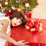 Child with gift box near Christmas tree. — Stock Photo