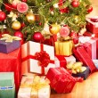 Foto de Stock  : Stack of gift box by Christmas tree.