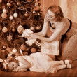 Kid with mother near Christmas tree. - Stock Photo