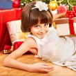Child with gift box near Christmas tree. - Stock Photo