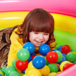 Little girl in group colourful ball. — Stock Photo