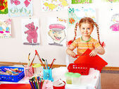 Child with scissors cut paper in playroom. — Stock Photo