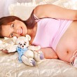 Pregnant woman holding teddy bear . — Stock fotografie