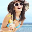 Girl in bikini drinking alcohol coctail through a straw. — Stock Photo