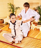 Male masseur doing massage woman in bamboo spa. — Стоковое фото
