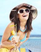 Girl in bikini drinking alcohol coctail through a straw. — Stock Photo