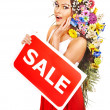 Woman holding sale banner and flower. — Stock Photo #19217199
