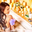 Stock Photo: Womusing bath sponge in bathtub.