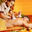 Stock Photo: Man getting herbal ball massage treatments .