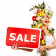 Woman holding sale banner and flower. — Stock Photo