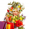 Woman with shopping bag holding flower. - Stock Photo
