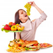 Woman choosing between fruit and hamburger. — Stockfoto