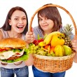 Stock Photo: Women choosing between fruit and hamburger.