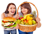 Women choosing between fruit and hamburger. — Stock Photo